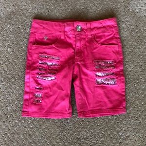Pink shorts with sequenced rips.